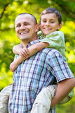 Fils de transport de père sur le sien en arrière Photographie stock libre de droits