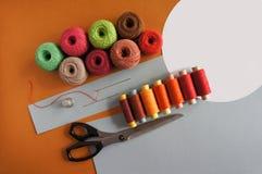 Fils des fils pour tricoter dans différentes couleurs sur un jaune et gris Photos libres de droits