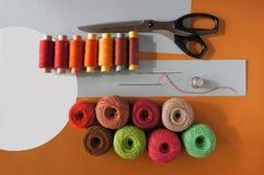 Fils des fils pour tricoter dans différentes couleurs sur un jaune et gris Images libres de droits