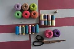 Fils des fils pour tricoter dans différentes couleurs sur un rose et un gris Photo libre de droits