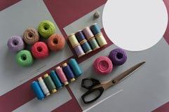 Fils des fils pour tricoter dans différentes couleurs sur un rose et un gris Photographie stock