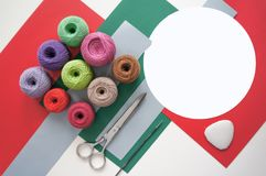 Fils des fils pour tricoter dans différentes couleurs sur un vert rouge Images stock