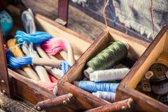 Fils et aiguilles colorés dans la boîte en bois du ` s de tailleur Photo stock