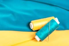 Fils et aiguilles colorés sur le textile Photographie stock