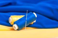 Fils et aiguilles colorés sur le textile Photo libre de droits