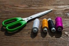 Fils et ciseaux multicolores de tailleur sur le fond en bois Photo stock