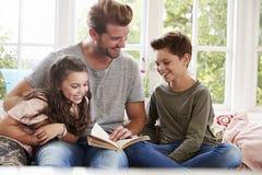 Fils et fille de Reading Book With de père à la maison photos stock