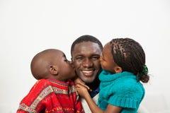Fils et fille embrassant son père Image libre de droits