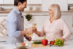 Fils heureux appréciant le vin avec son parent dans la cuisine Images libres de droits