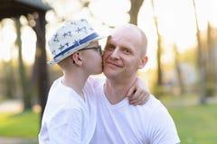 Fils heureux d'enfant embrassant le père Photo stock
