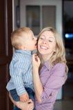Fils heureux de famille embrassant la mère Photos libres de droits