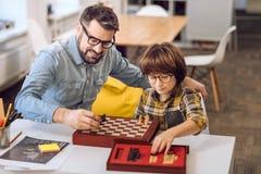 Fils heureux et père étendant des échecs sur le bureau images stock