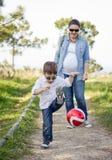 Fils heureux jouant avec du ballon de football, et son regard de mère de pregnacy Image libre de droits