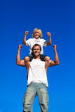 Fils intense s'asseyant sur les épaules de son père images stock