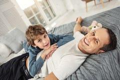 Fils joyeux et papa détendant sur le lit Photos stock
