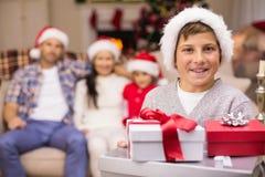 Fils joyeux tenant la pile des cadeaux avec sa famille derrière Photos stock