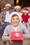Fils joyeux tenant le cadeau devant sa famille Images stock
