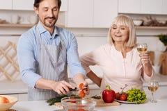 Fils mûr faisant cuire le dîner pour son parent dans la cuisine Photo stock