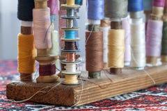 Fils multicolores de couture de couleurs en pastel douces de vintage sur le spo Photographie stock libre de droits