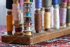 Fils multicolores de couture de couleurs en pastel douces de vintage sur le spo Images stock