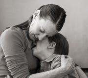 Fils pleurant d'étreintes de mère image stock
