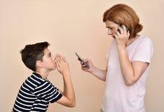 Fils priant sa mère fâchée et nerveuse pour l'attention photos stock