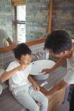 Fils se brossant les dents avec le père dans la salle de bains Photo stock
