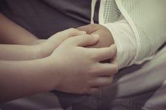 Fils tenant la main de son père qui a un accident Photo libre de droits