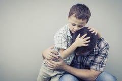 Fils triste étreignant son papa près du mur photo libre de droits