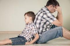 Fils triste et son papa s'asseyant sur le plancher à la pièce au temps de jour images stock