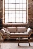 Filt på beige soffa och trätabell på matta i vindvardagsrum som är inre med fönstret arkivfoto