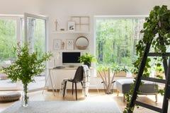 Filt på stol bredvid skrivbordet i ljus vardagsruminreintelligens royaltyfria bilder
