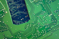 Filtered green computer motherboard circuit above blue motherboard hole Royalty Free Stock Photography