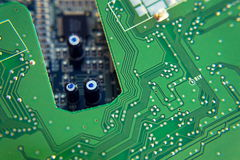 Filtered green computer motherboard circuit above blue motherboard hole Royalty Free Stock Photo