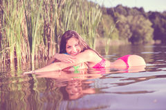 Filtered image of sexy beautiful brunette young woman in pink bikini having fun in water at sunset on green summer outdoors copy s Royalty Free Stock Image