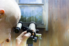 Man Spying At Telescope. Filtered photo of a man spying at telescope, a window in the background outdoor cropped shot Royalty Free Stock Images