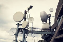 Filtered picture of security camera with transmitters and aerials on telecommunication tower Stock Photo