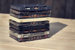 Filtered retro compact cassette audio tapes on wooden background Royalty Free Stock Image