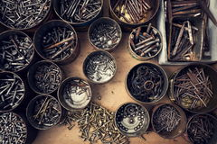 Filtered screws and bolts in tin can on wooden background Royalty Free Stock Images