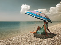 Filtered view of a girl, umbrella and beach Stock Photos