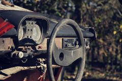Filtered vintage photo of steering wheel and rusty speedometer on dashboard Royalty Free Stock Images