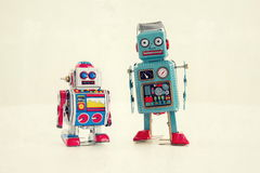Filtered vintage tin toy robots isolated on white background Stock Images