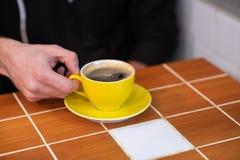 Filterkoffie in een gele die kop, door mensenhanden wordt gehouden royalty-vrije stock fotografie