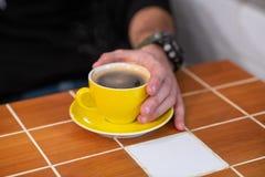 Filterkoffie in een gele die kop, door mensenhanden wordt gehouden royalty-vrije stock afbeeldingen