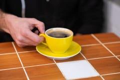 Filterkoffie in een gele die kop, door mensenhanden wordt gehouden stock foto