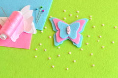 Filtfjärilen, pappers- mallar, tråden, visare, klämmer fast, pärlor, blått, och rosa färgen täcker på en grön bakgrund Sy uppsätt Royaltyfri Foto