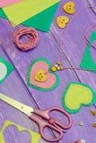 Filthjärtahalsband Halsband för dag för valentin` som s göras av filt, pärlor och en träknapp Hantverktillförsel på en trätabell Royaltyfri Fotografi