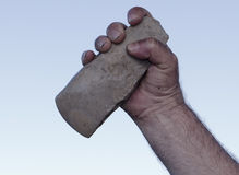 Filthy hand holding handaxe Stock Images