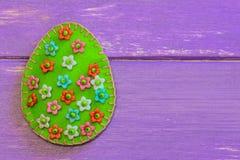Filtpåskägg med plast- blommor Filtägg på purpurfärgad träbakgrund med kopieringsutrymme för text kort lyckliga easter Royaltyfria Bilder