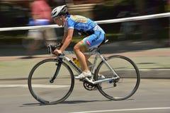 Filtração de uma bicicleta bonita da equitação da menina em um dia ensolarado, competindo para o evento grande de Prix da estrada Fotografia de Stock
